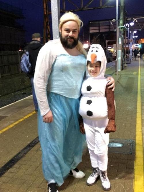 Un hombre abrazando a su hija disfrazados de personajes de la película frozen