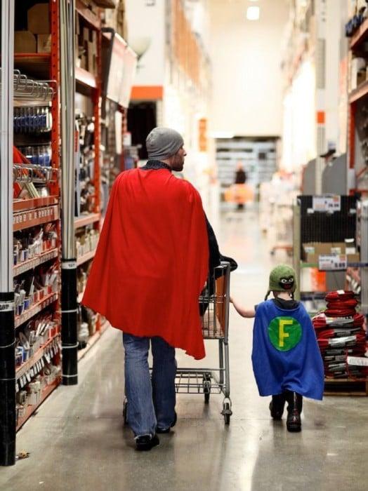 Padre e hijo disfrazados de superhéroes caminando por le pasillo de un centro comercial