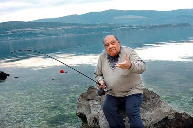 Hombre sentado sobre una roca con una caña de pescar sobre un río