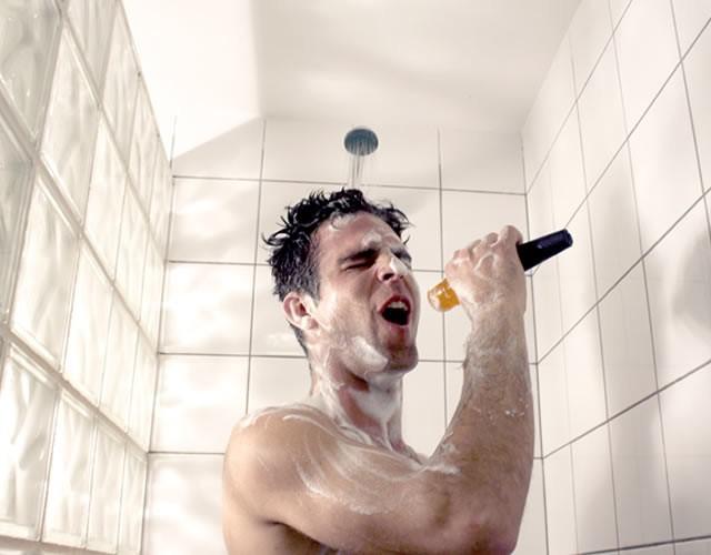 Chico dentro del baño cantando bajo la ducha con un poco de jabón