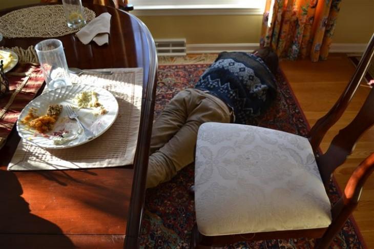 Hombre acostado en el piso debajo de una mesa después de comer