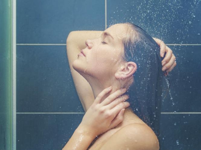 Chica mirando hacia arriba bajo la ducha