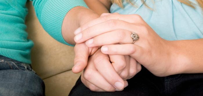 Una mano encima de la otra de dos personas juntas