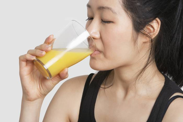 Una chica tomando jugo de naranja
