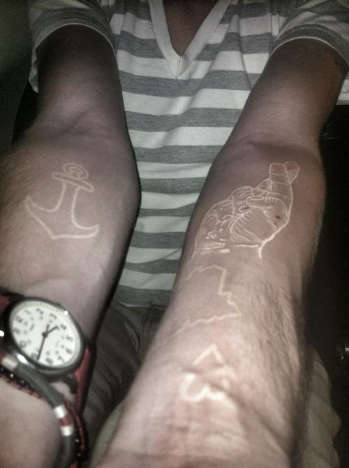 Tatuaje con tinta blanca sobre los brazos