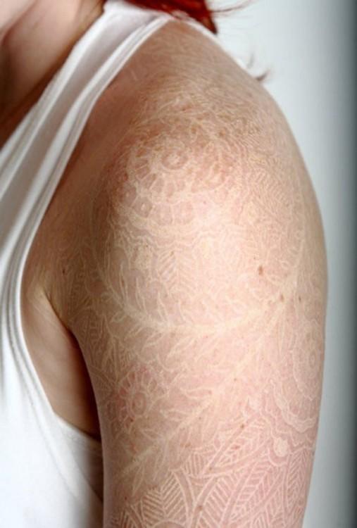 Tatuaje en el hombro de una chica con tinta blanca
