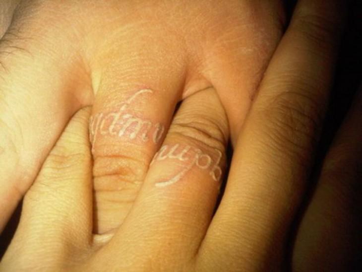 Tatuajes con tinta blanca sobre los dedos de una persona