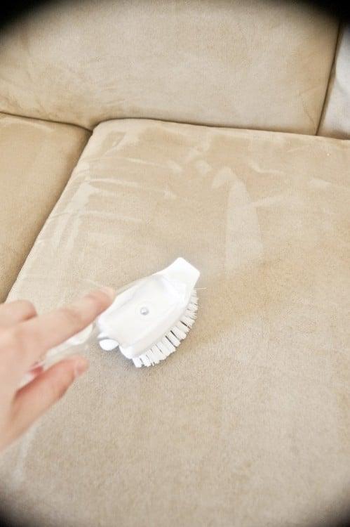 Cepillo de cerdas blancas limpiando un sofá de microfibra