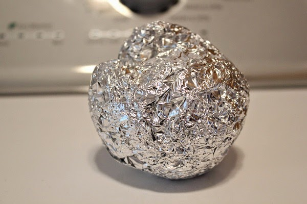 Bola de papel aluminio sobre una superficie en color blanco