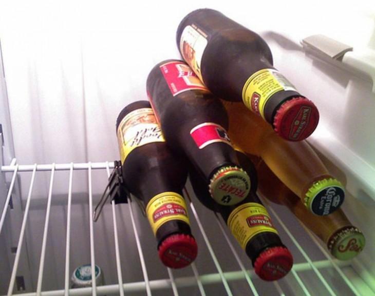 Botellas de cerveza apilas en una pirámide con un clip sujeta papeles en una balda del refrigerador