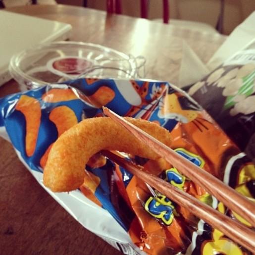 Palillos chinos sosteniendo un cheeto sobre una bolsa de sabritas