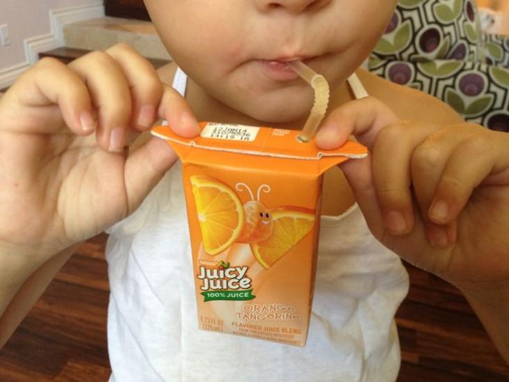 Niño sosteniendo su jugo de las solapas de los costados