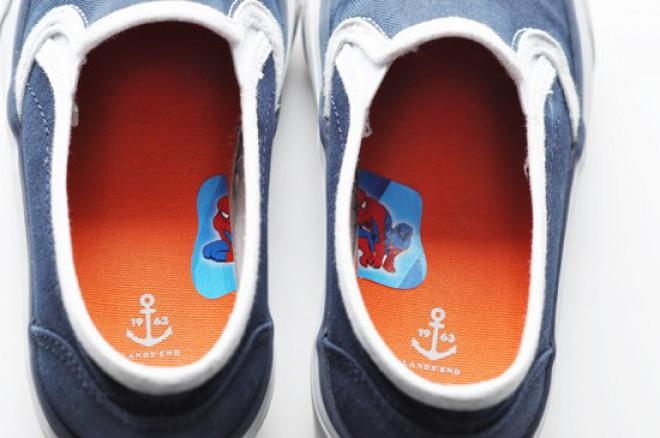 Zapatos de un niño con la mitad de una calcomanía en el pie izquierdo y la otra mitad en el derecho