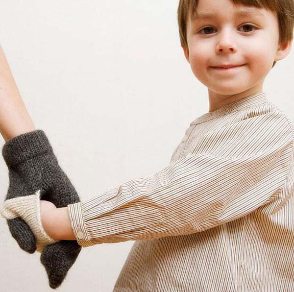 Un niño agarrado de la mano de su mamá a través de un guante