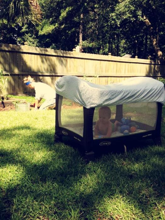 Corralito de bebé con una sábana encima en un jardín