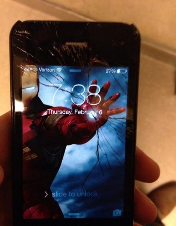 Un celular con la pantalla estrellada con un Wallpaper de Iron Man