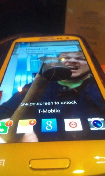 fondo de pantalla de un hombre que simula estar golpeando el celular con un martillo