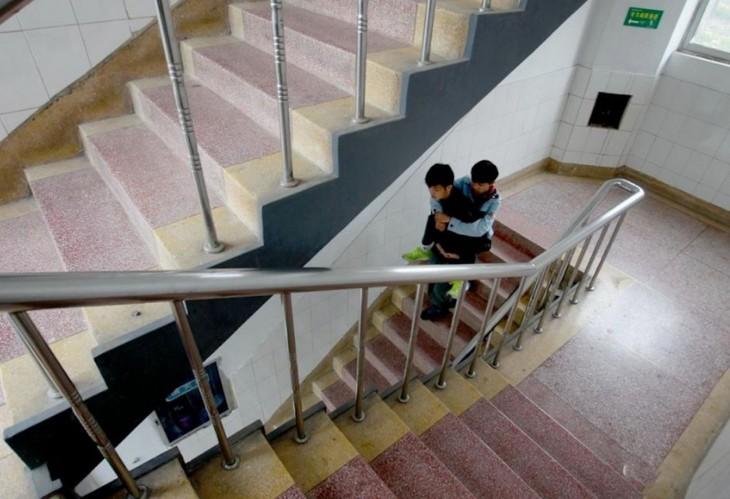 xie lleva en la espalda a su amigo zhang mientras bajan las escaleras de su escuela