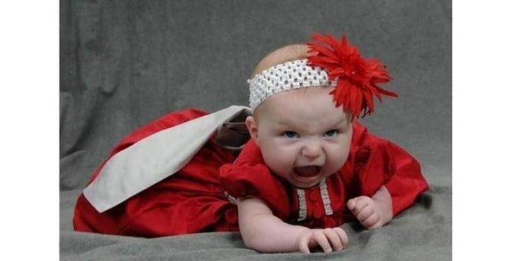 bebé vestida de rojo y gritando