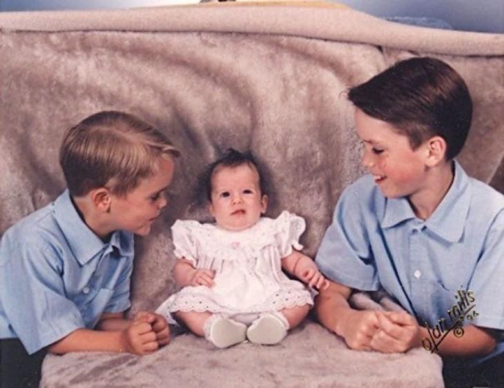 hermanos con su hermana bebé sentada