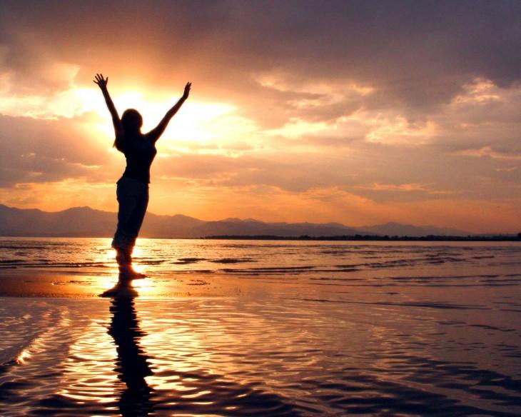 chica estira los brazos, haciendo yoga al atardecer en la playa