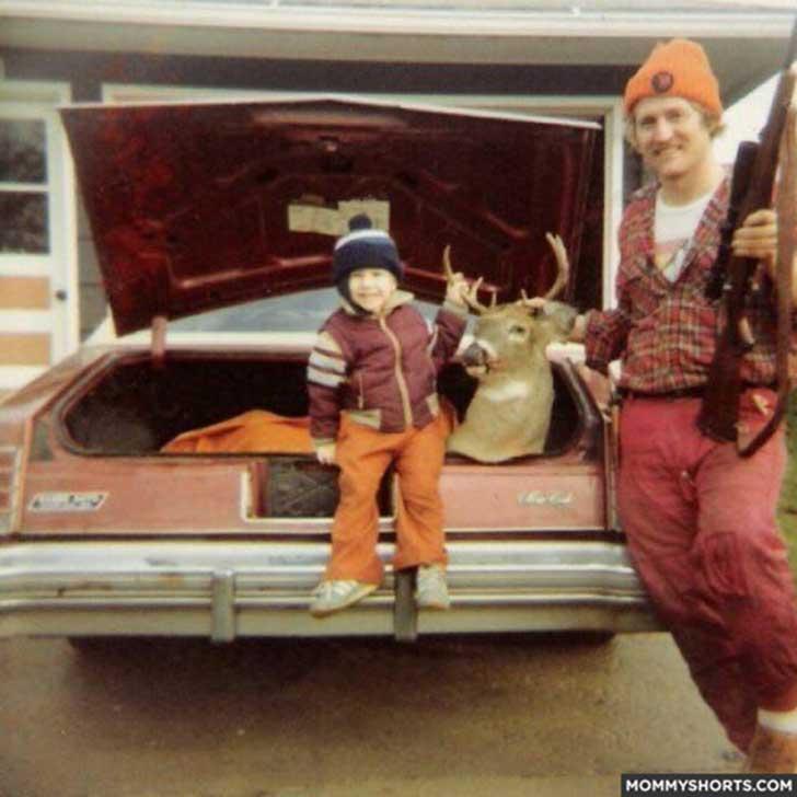 padre e hijo pequeño con escopeta y ciervo muerto