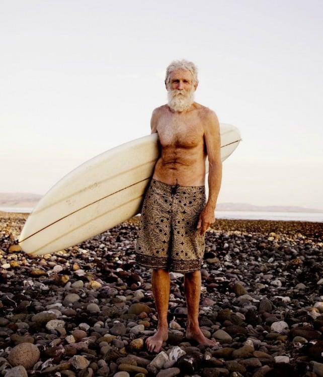 abuelo surfeando en playa llena de piedras