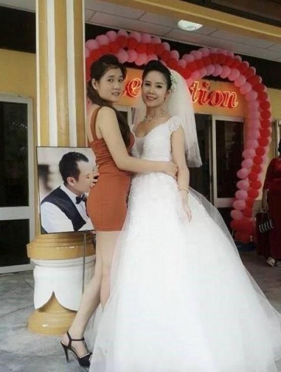 Dos chicas abrazadas con un retrato detrás de en donde el chico de la foto simula besar su mano