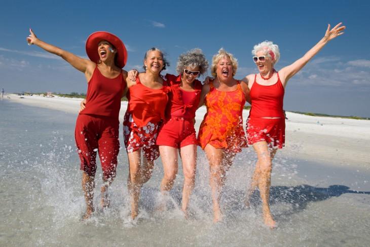 mujeres adultas mayores en la playa vestidas de rojo