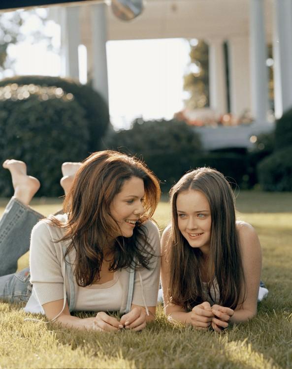 madre y su hija recostadas en el pasto platicando