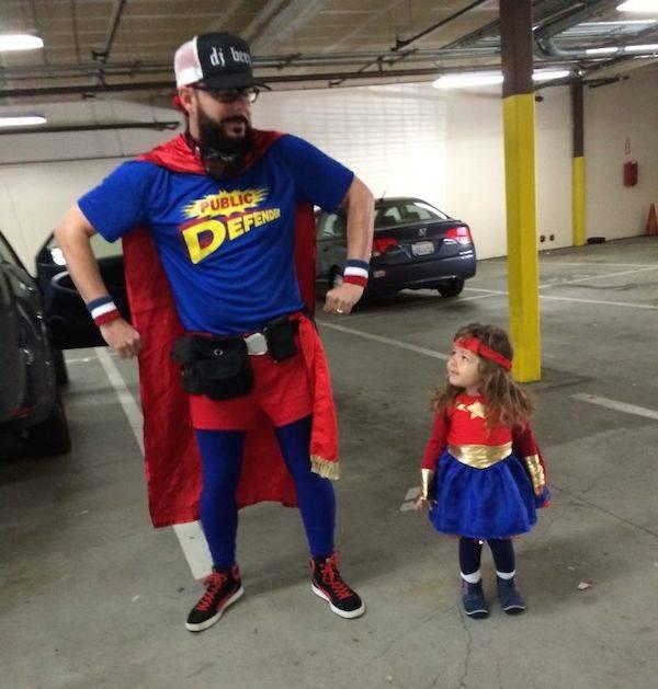 Padre a un costado de su hija vestidos de superhéroes