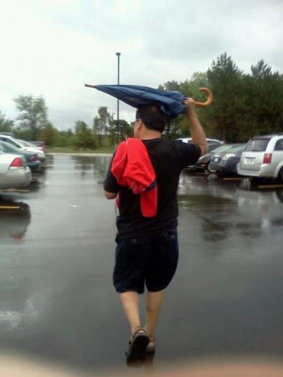 Señor con paraguas en estacionamiento