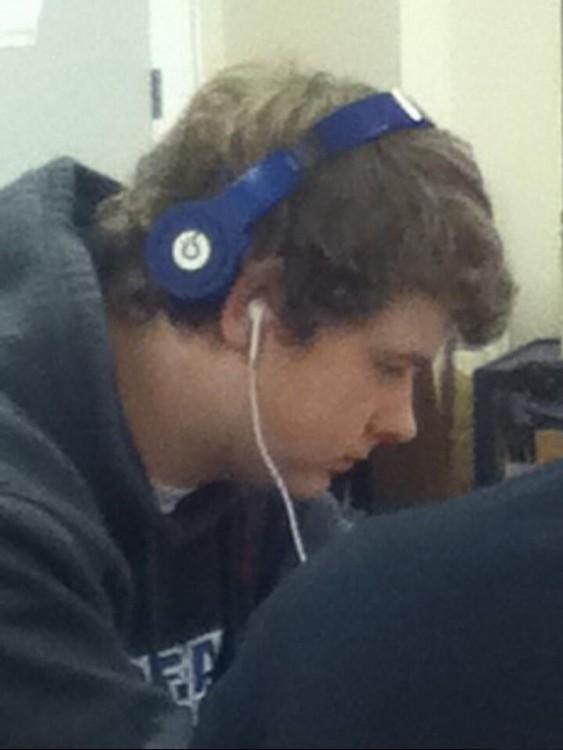 Chico escuchando música con dos auriculares
