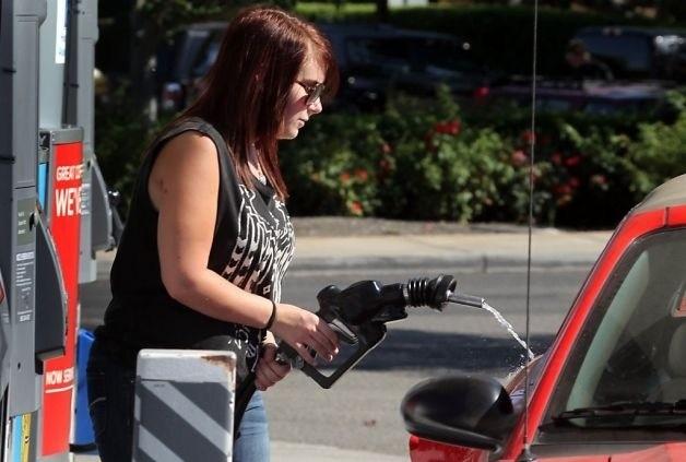 Chica intentando poner gasolina
