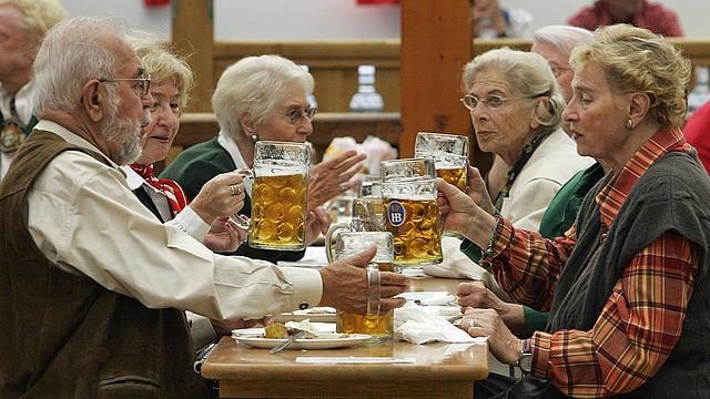 adultos mayores tomando  cerveza en ocktoberfest