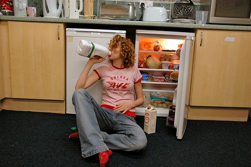 mujer tomando leche tirada en el piso