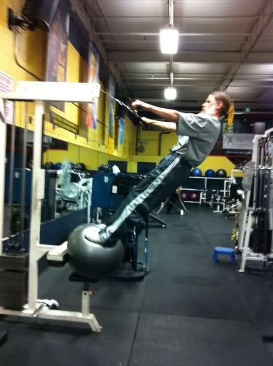 hombre arriba de pelota de yoga para hacer brazo