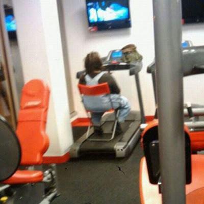 mujer sentada en una silla arriba de caminadora viendo la tele en el gimnasio