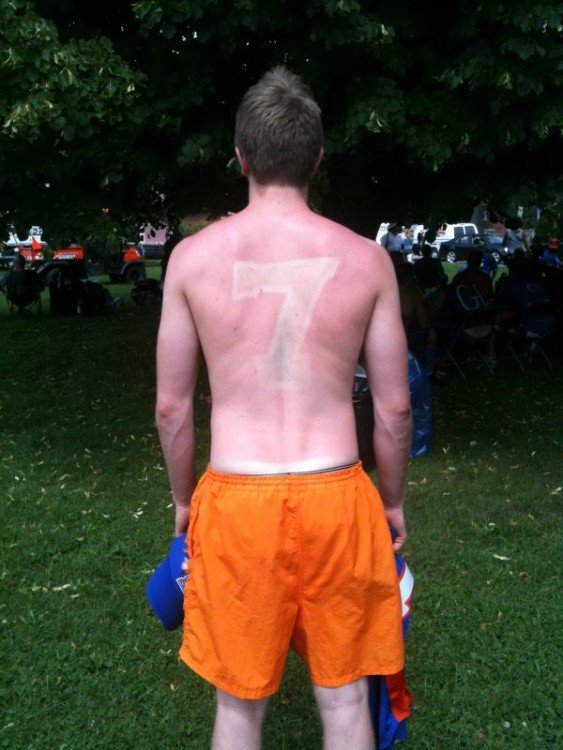 hombre se tataua con el sol el numero 7 en su espalda