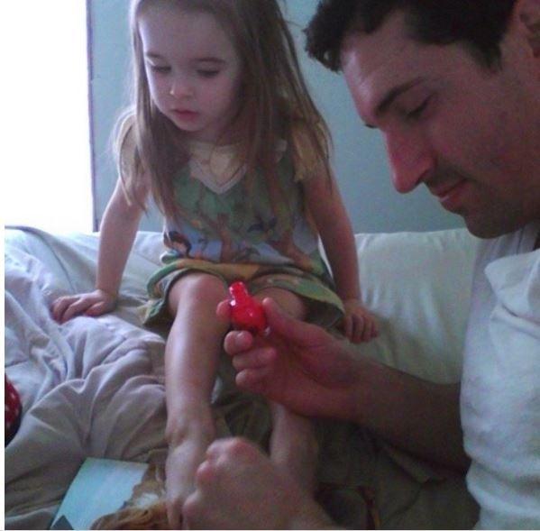 padre le pinta las uñas a la hija y la niña no esta muy convencida