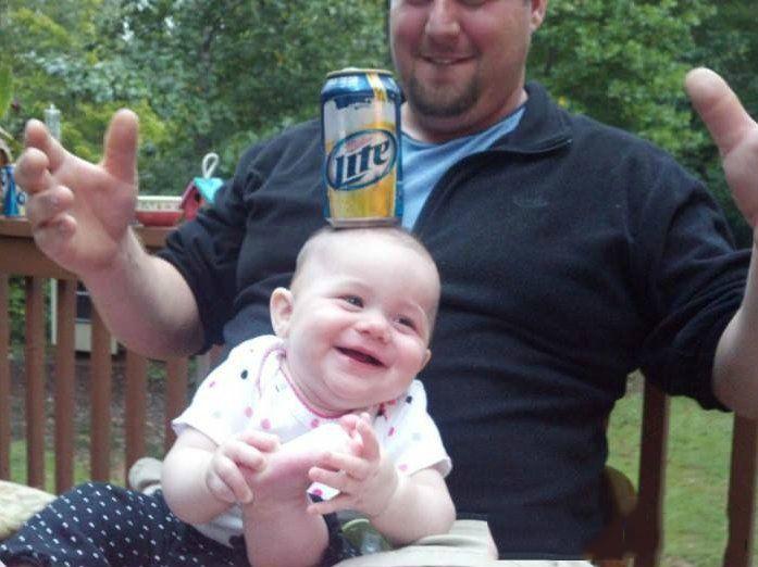 niño soteniendo cerveza con la cabeza y papa jugando con el