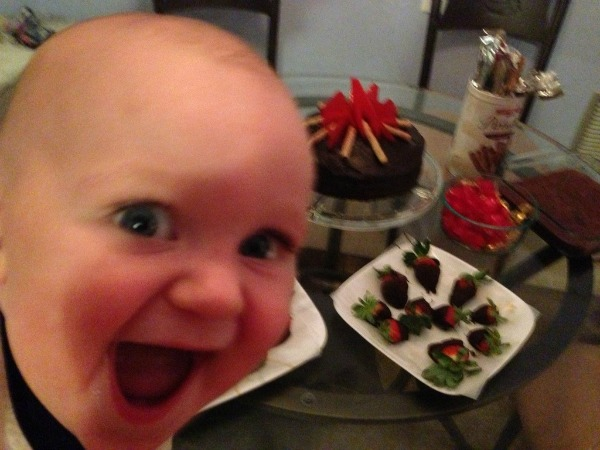 niño feliz por ver las fresas en la mesa