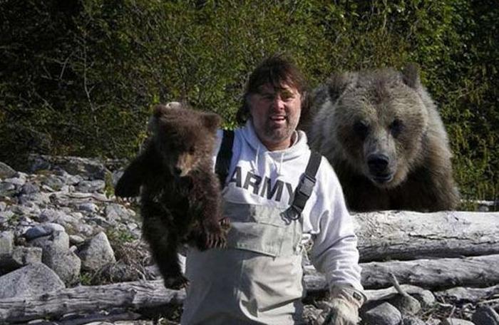 tipo cargando a oso bebe y detras esta la mama