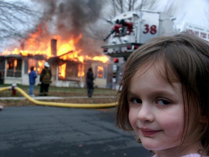 niña con los bomberros e incendio de fondo