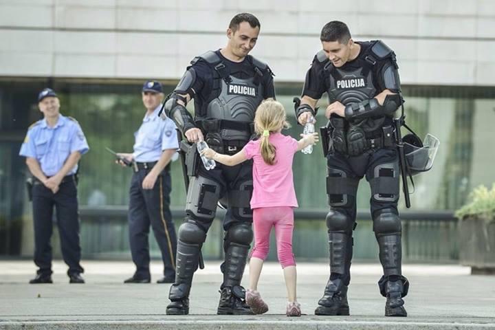 Niña ofrece agua a policías, Bosnia 2013
