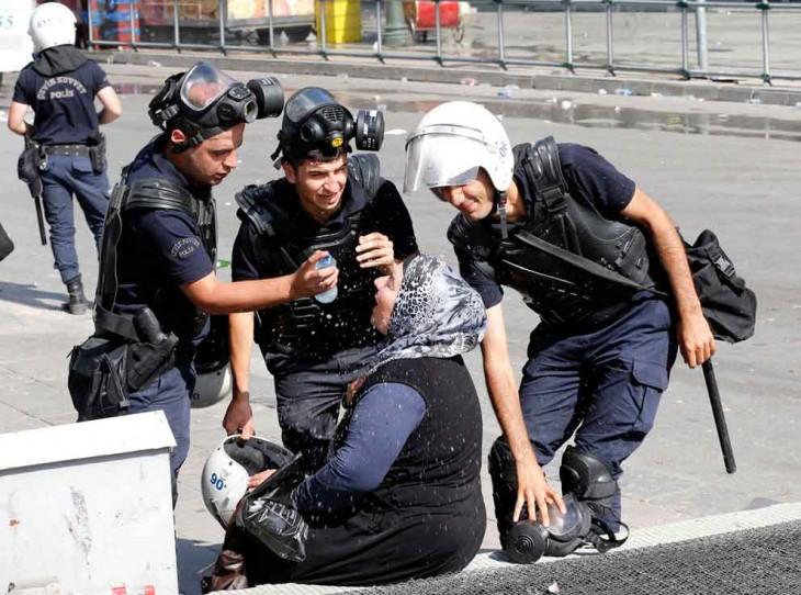 Policías ayudan a mujer a limpiar sus ojos del gas lacrimógeno, Turquía 2013