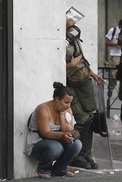 Manifestantes griegos y la policía se toman un descanso para fumar un cigarrillo juntos durante las protestas de austeridad. Atenas, Grecia, 2011.