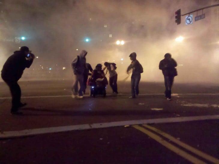 manifestantes sacan del gas lacrimogeno a mujer en silla de ruedas en oakland 2011