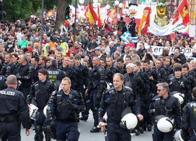 Oficiales anti disturbios se sacan sus cascos y escoltan a los manifestantes. Frankfurt, Alemania, 2011.