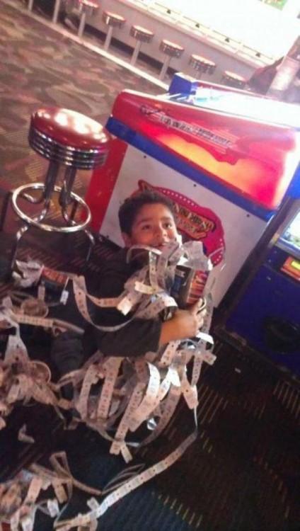 niño feliz de haber ganado infinidad de tickets en su maquina favorita